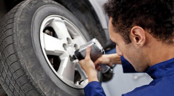 Auto Mechanic Repairing Car Tire